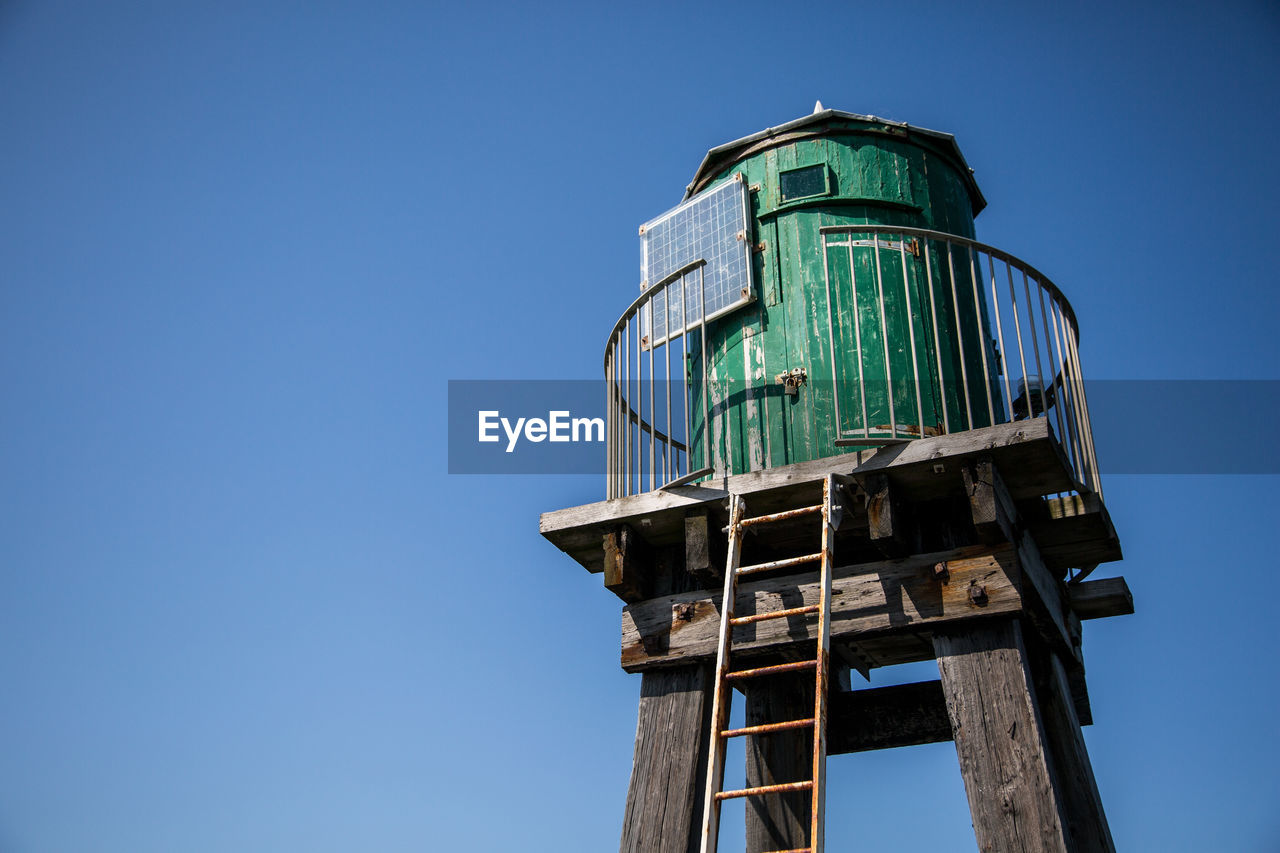 low angle view, sky, architecture, clear sky, built structure, copy space, blue, building exterior, nature, no people, tower, day, old, building, sunlight, window, outdoors, metal, abandoned, tall - high, turquoise colored