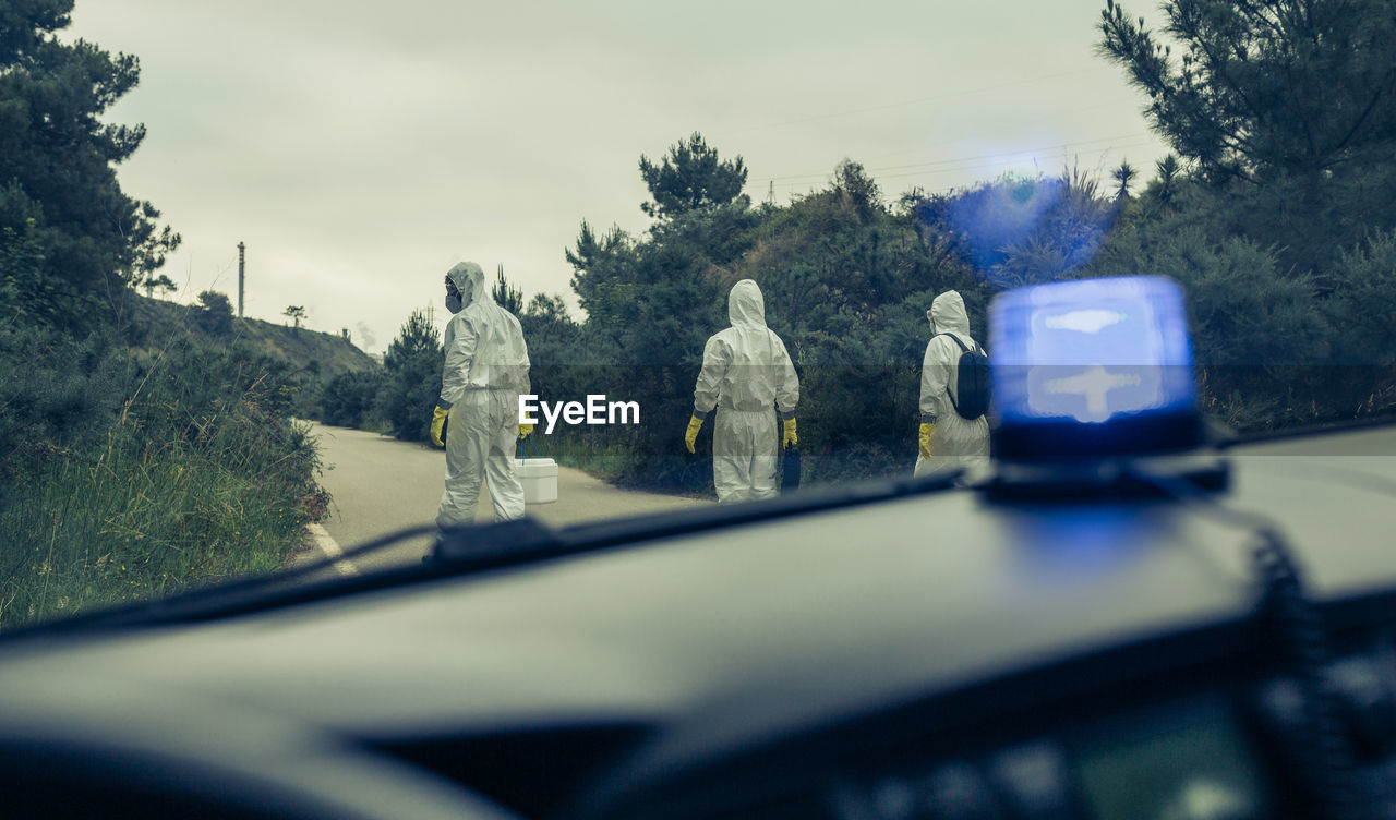 Rear view of people wearing protective suit walking on road seen through car
