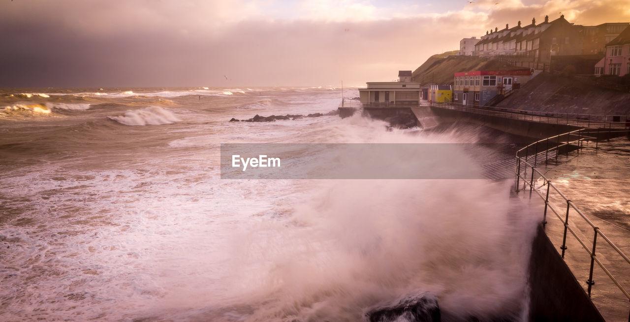 Waves Splashing On Pier During Sunset
