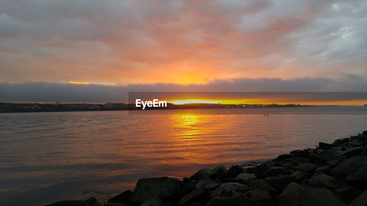 sunset, scenics, beauty in nature, sea, nature, sky, water, tranquil scene, tranquility, cloud - sky, idyllic, orange color, dramatic sky, no people, rock - object, outdoors, horizon over water, day