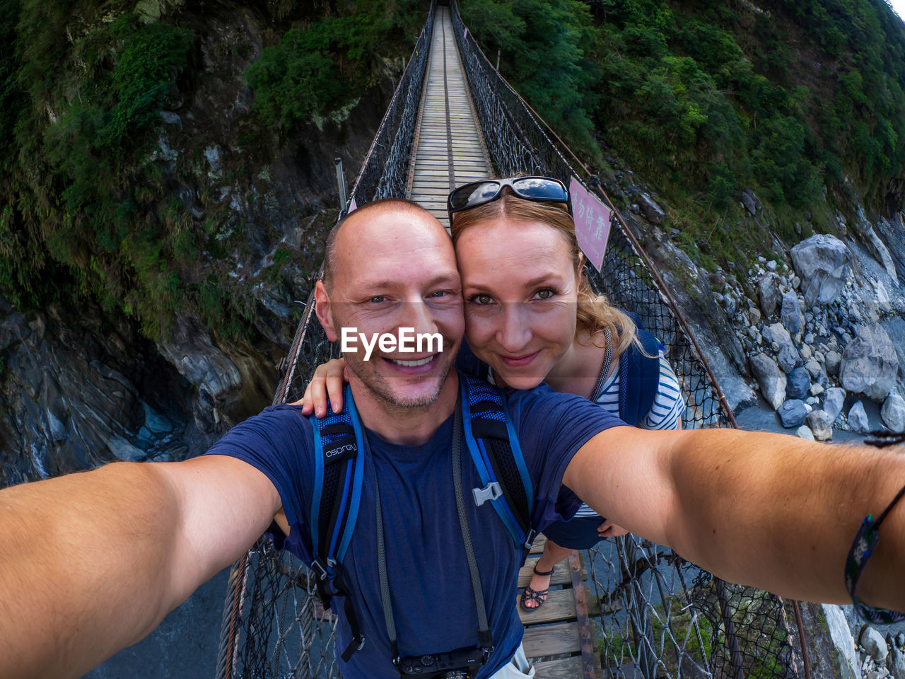 portrait, selfie, camera, looking at camera, two people, wireless technology, photography themes, smiling, togetherness, leisure activity, men, technology, adult, emotion, happiness, lifestyles, bonding, adventure, self portrait photography, real people, couple - relationship, positive emotion, outdoors