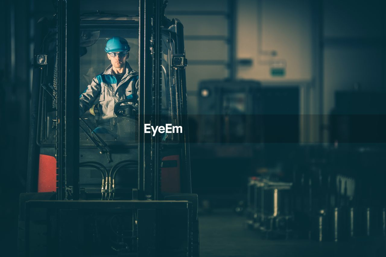 Worker Riding Forklift In Factory
