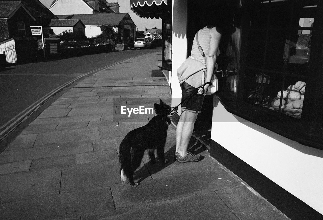 Full length of woman with dog standing near door at sidewalk