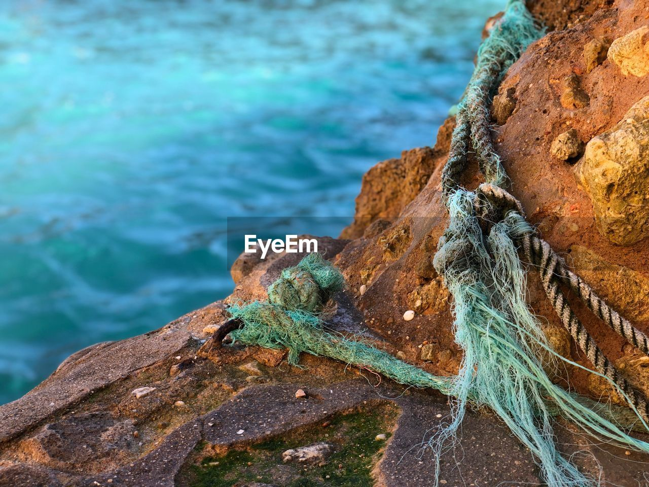 rock, water, sea, rock - object, solid, rope, strength, close-up, day, no people, focus on foreground, nature, textured, outdoors, beach, tied up, high angle view, metal, rough, turquoise colored