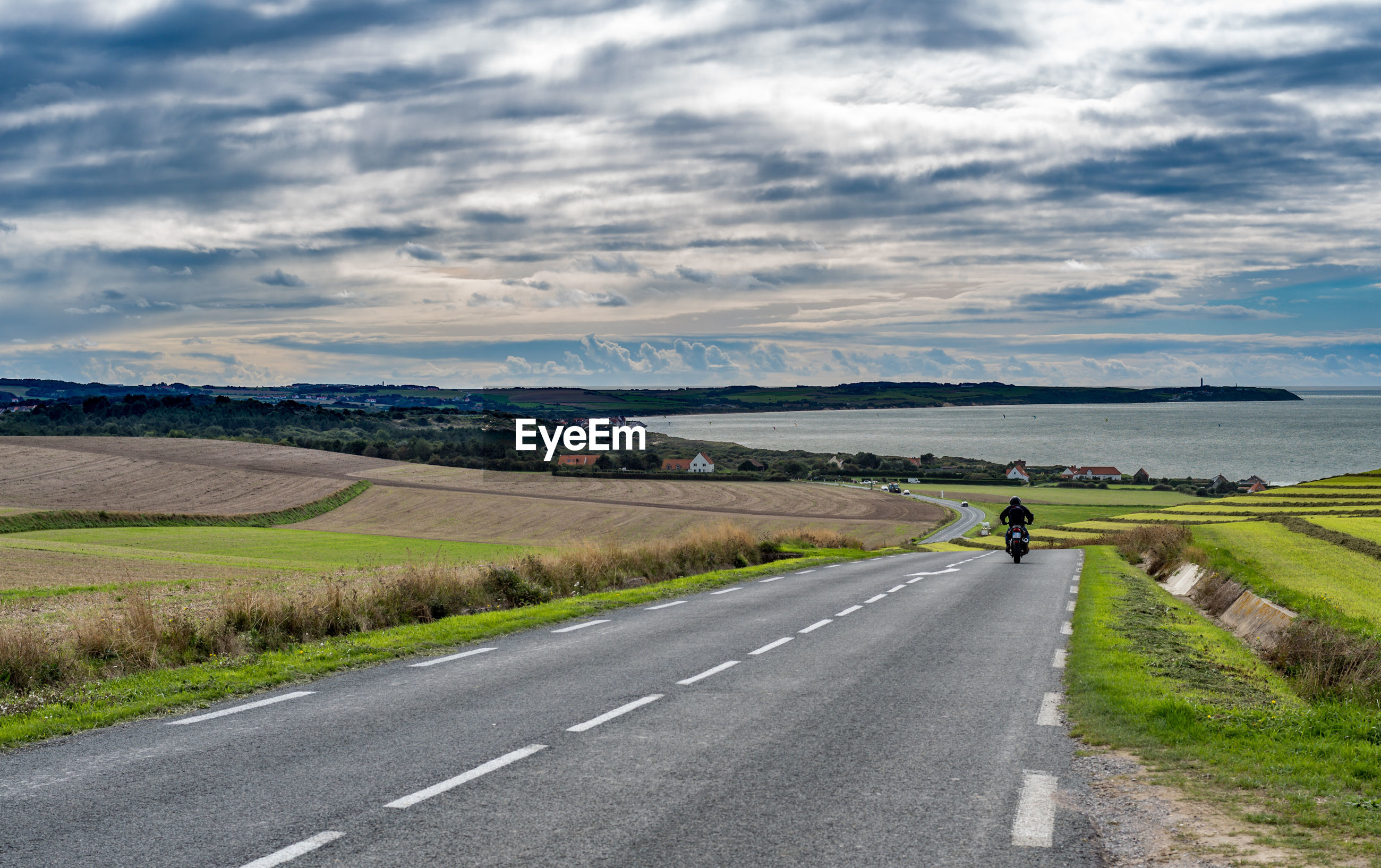Man riding motorcycle on country road against cloudy sky