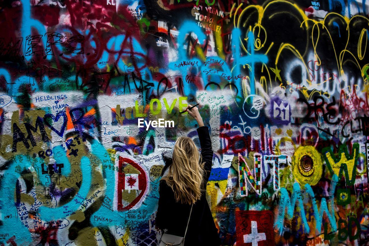 Rear View Of Woman Painting On John Lennon Wall