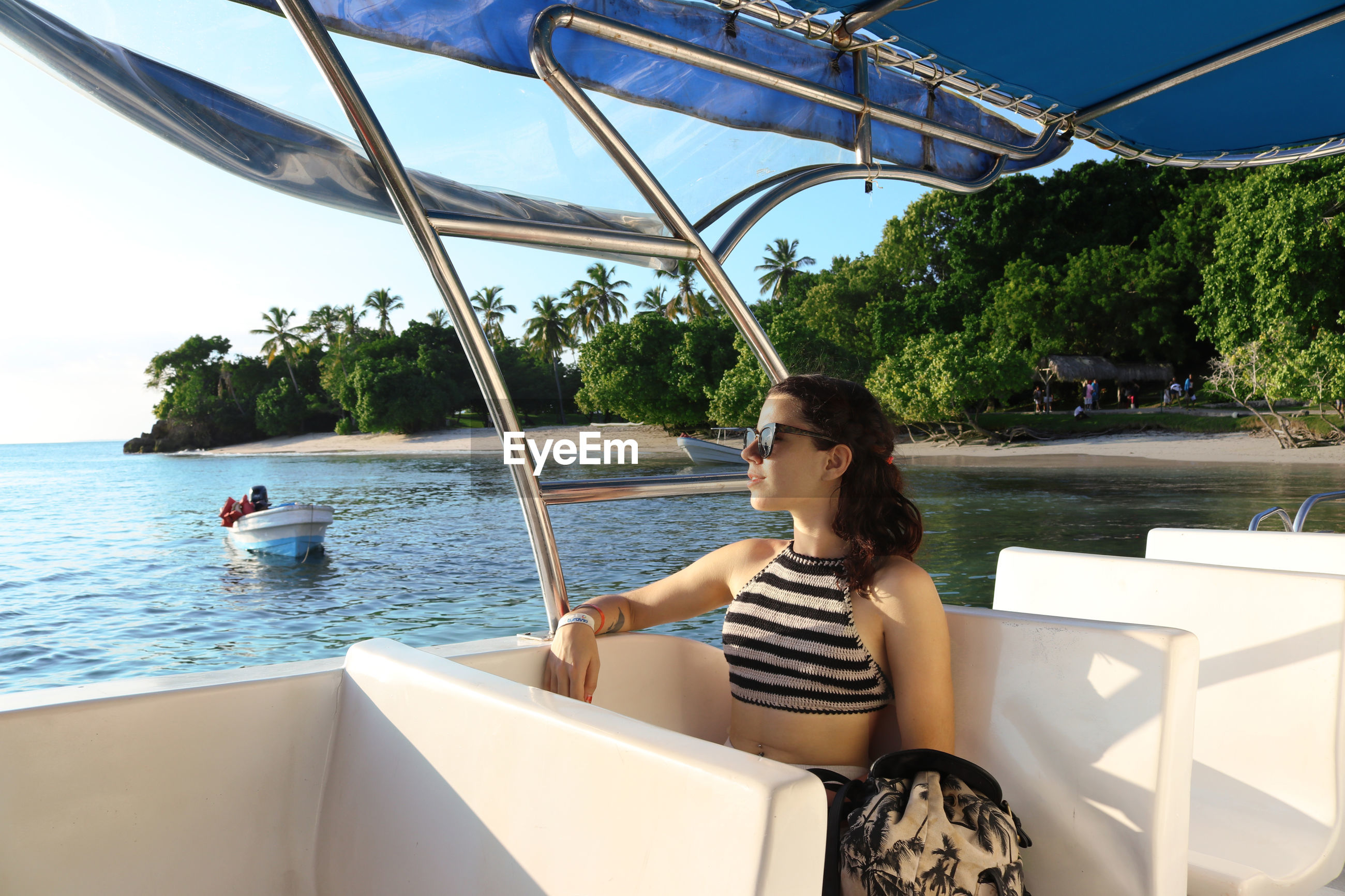 WOMAN SITTING ON BOAT AGAINST TREES