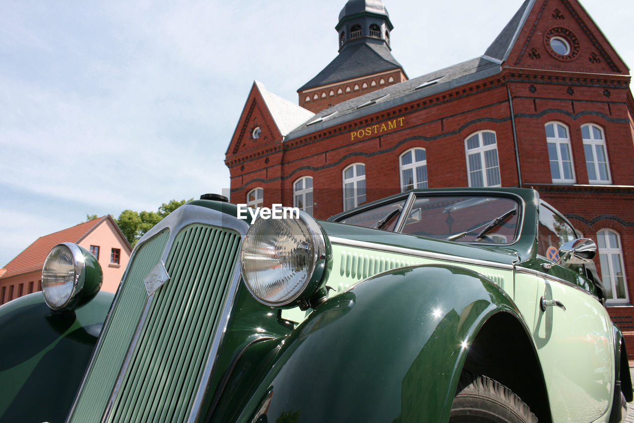 mode of transportation, car, transportation, motor vehicle, day, sky, land vehicle, building exterior, built structure, vintage car, retro styled, architecture, nature, no people, building, cloud - sky, headlight, history, travel