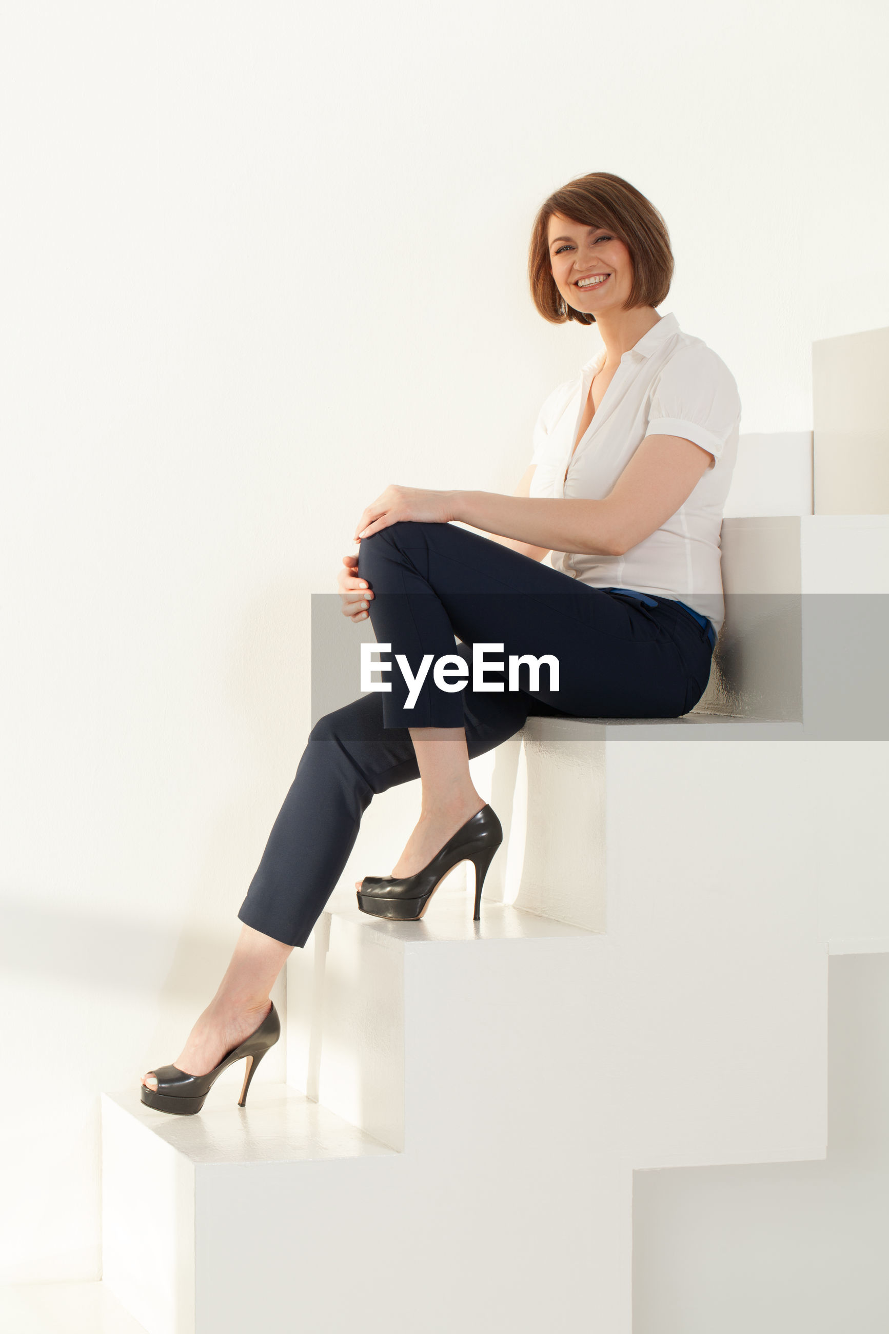 Portrait of confident businesswoman sitting on steps in office