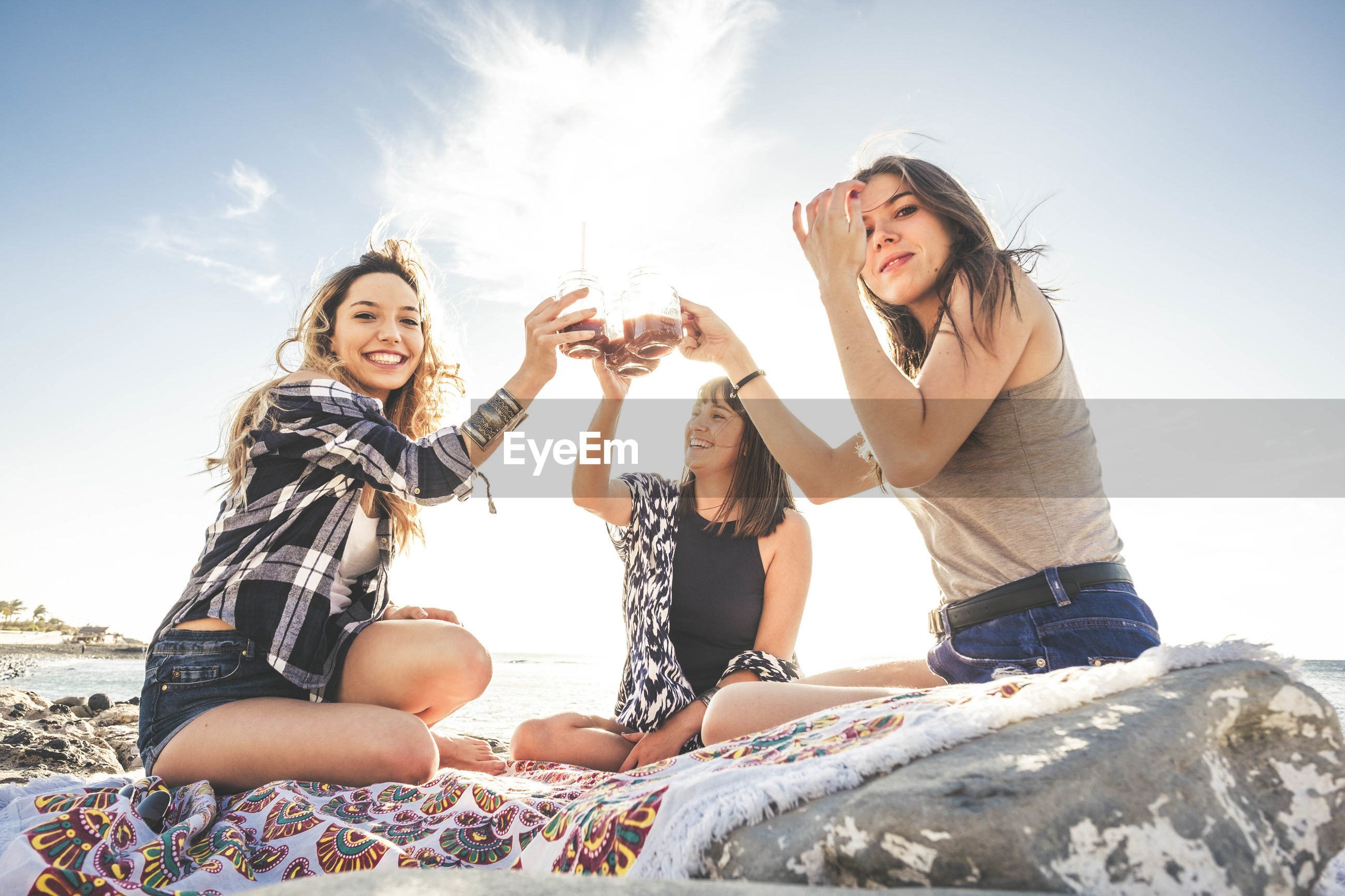 Happy friends having drink while sitting on textile at beach