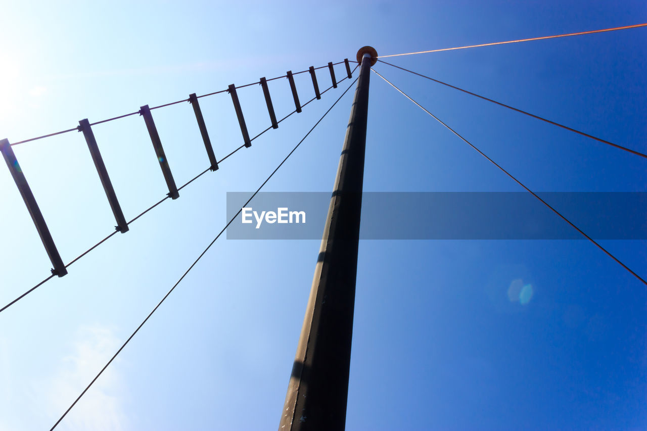 low angle view, sky, blue, cable, no people, connection, nature, technology, electricity, pole, day, metal, power supply, lighting equipment, power line, outdoors, fence, bridge, barrier, built structure, telephone line, electrical equipment