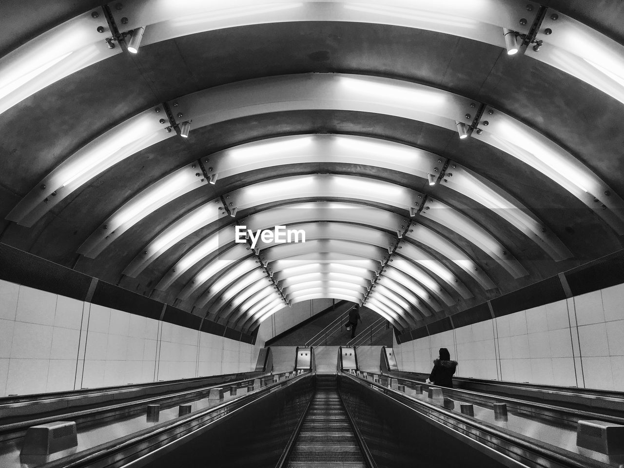 architecture, indoors, transportation, the way forward, built structure, direction, ceiling, diminishing perspective, incidental people, illuminated, subway station, real people, public transportation, arch, subway, walking, modern, technology, travel, railing, moving walkway