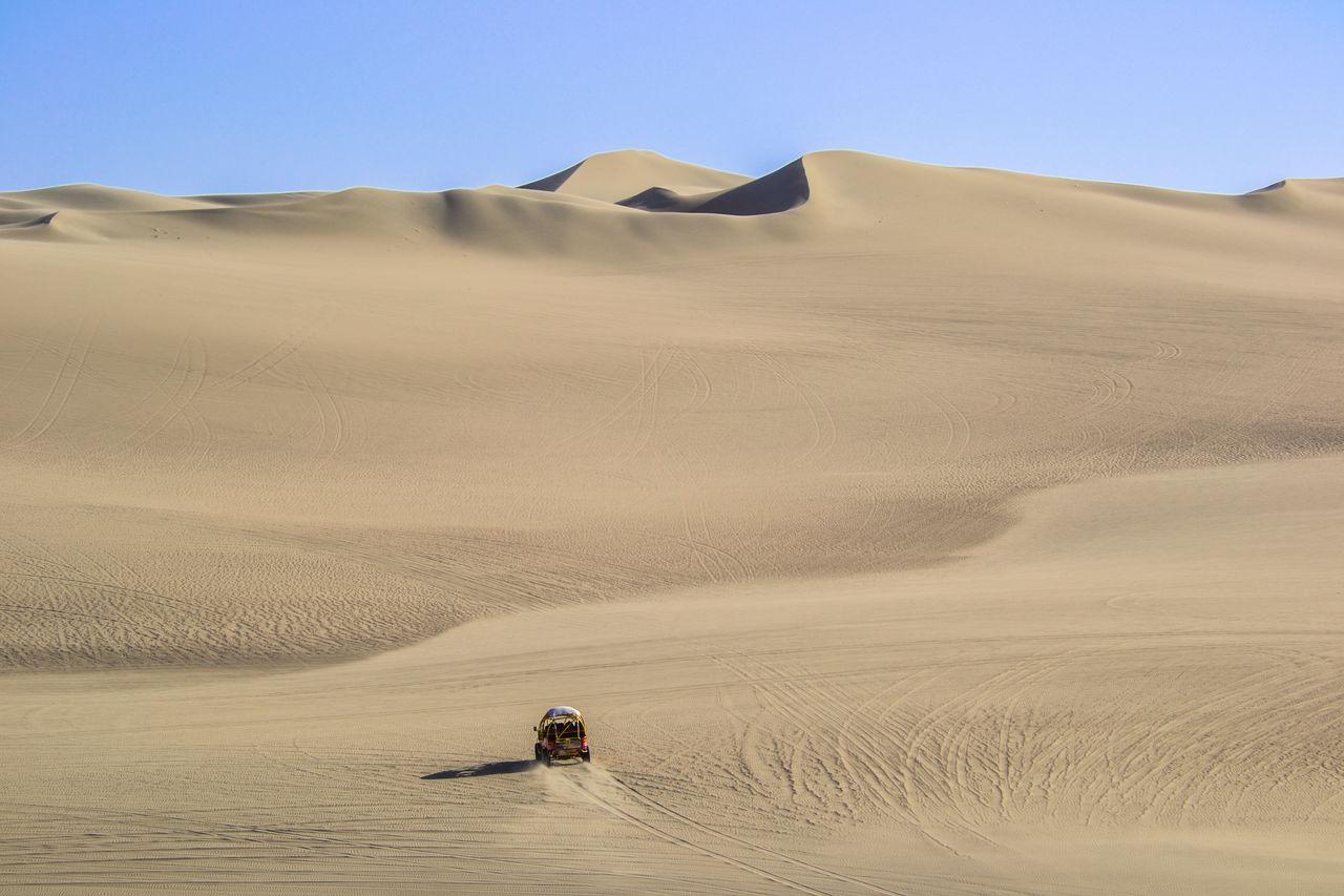Vehicle In Desert Against Sky