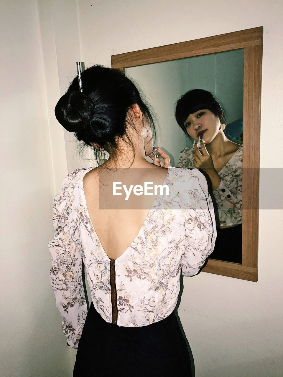 Portrait of woman doing makeup in front of mirror