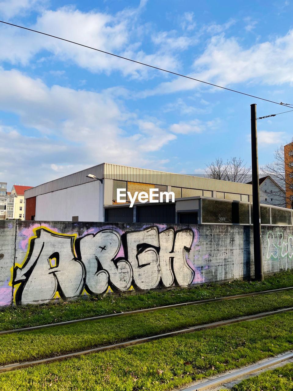 GRAFFITI ON RAILROAD TRACKS AGAINST SKY
