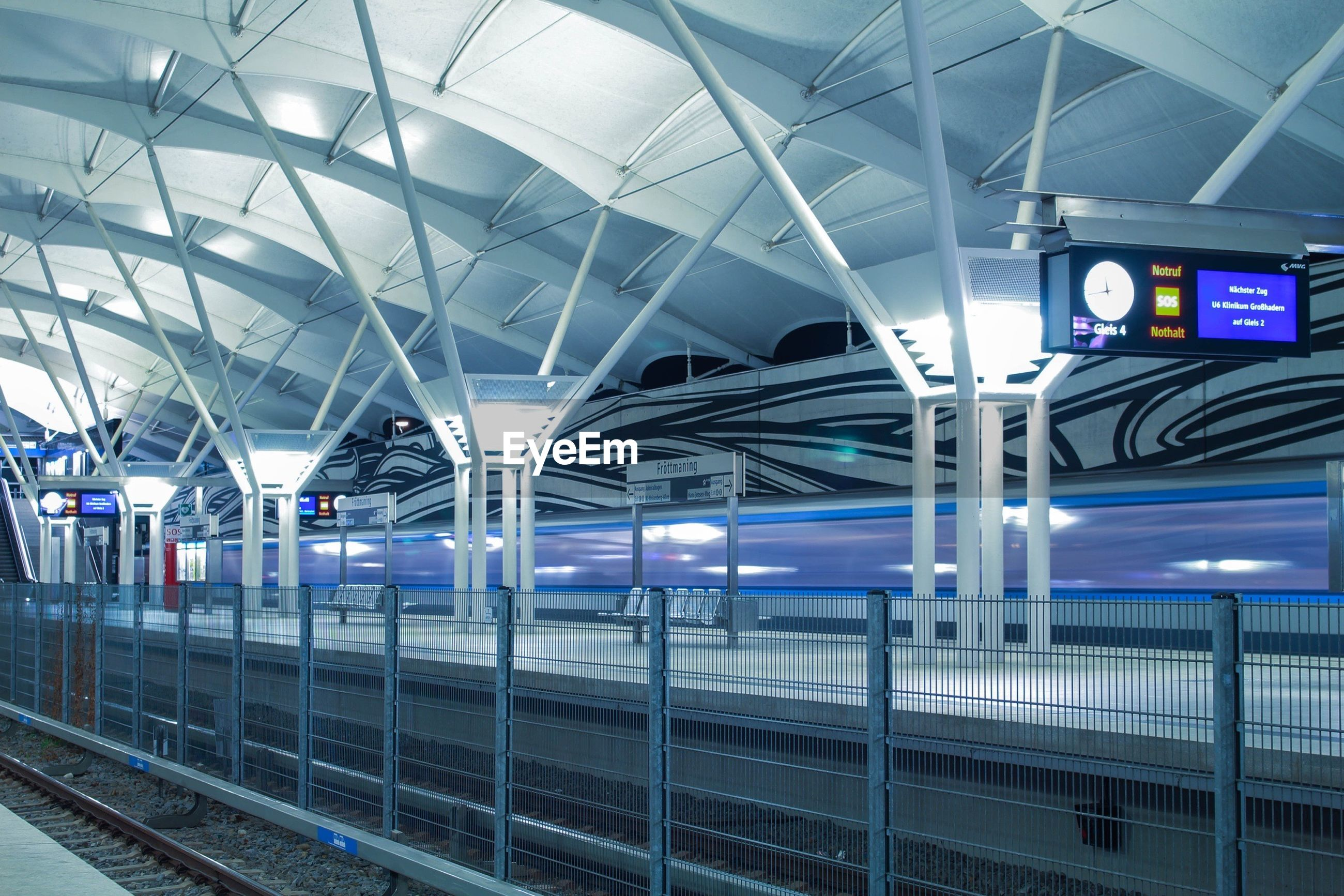 railroad station, indoors, public transportation, transportation, railroad station platform, rail transportation, train - vehicle, subway station, architecture, built structure, transportation building - type of building, ceiling, travel, railroad track, text, interior, passenger train, western script, mode of transport, station