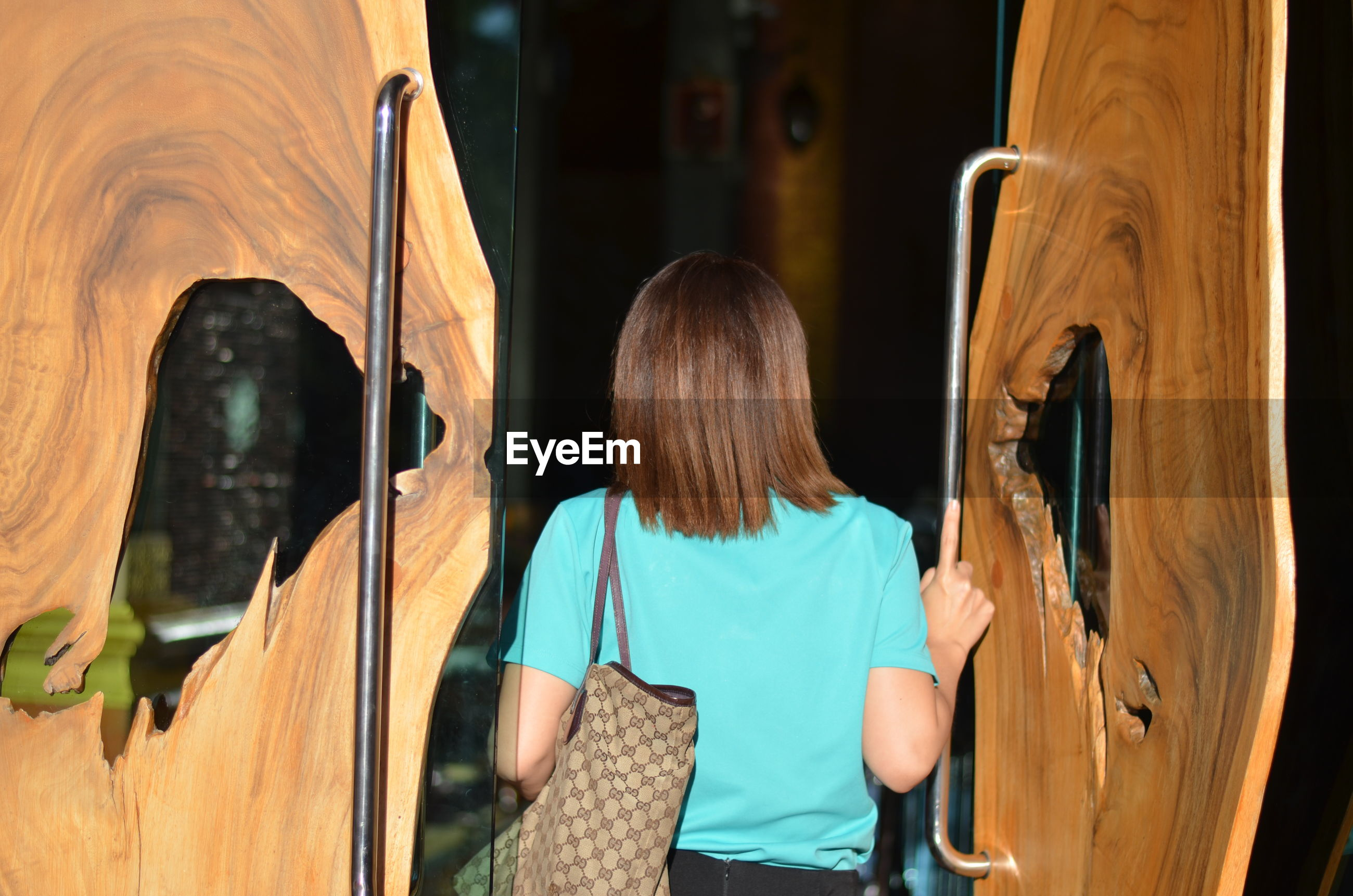Rear view of woman carrying bag while entering restaurant