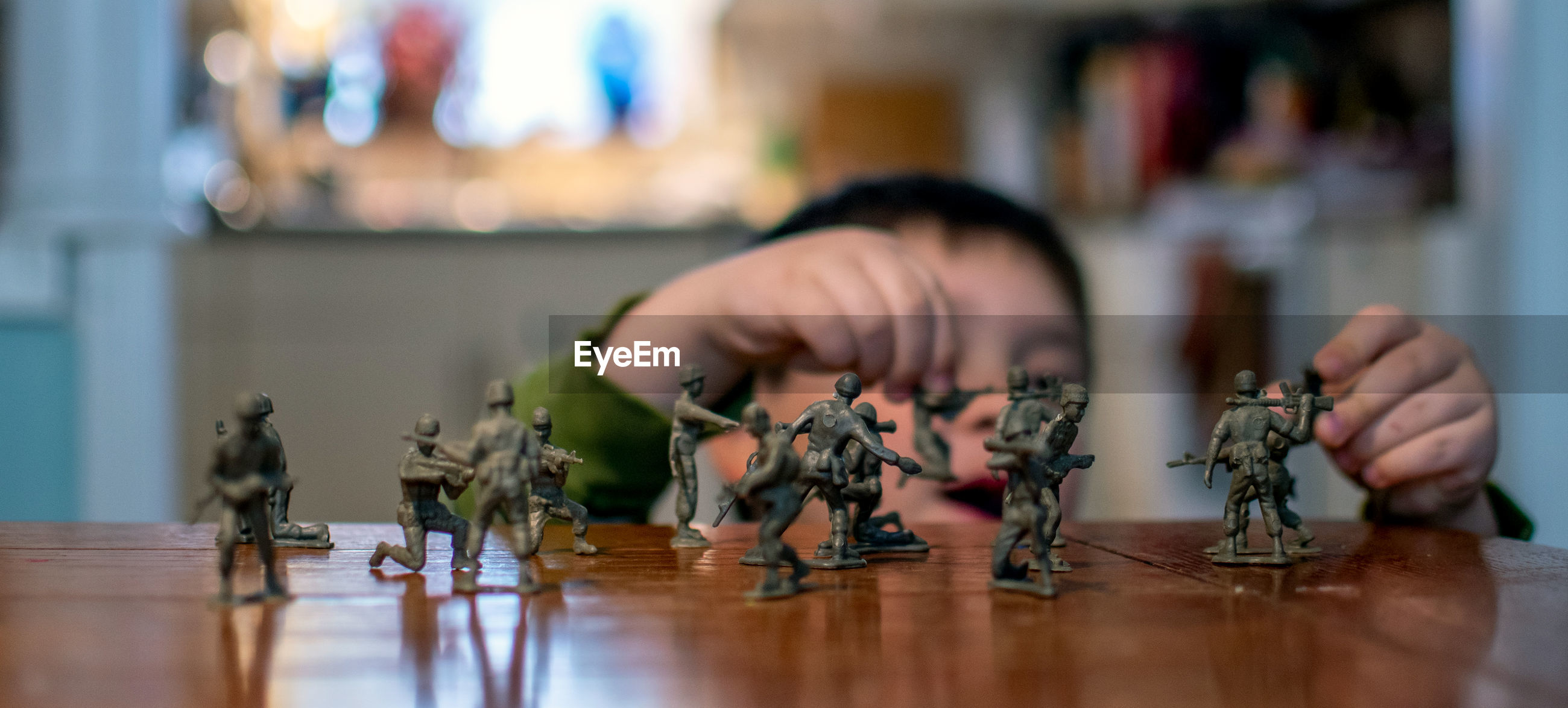Small hands move toy soldiers around a mock battle on a tabletop