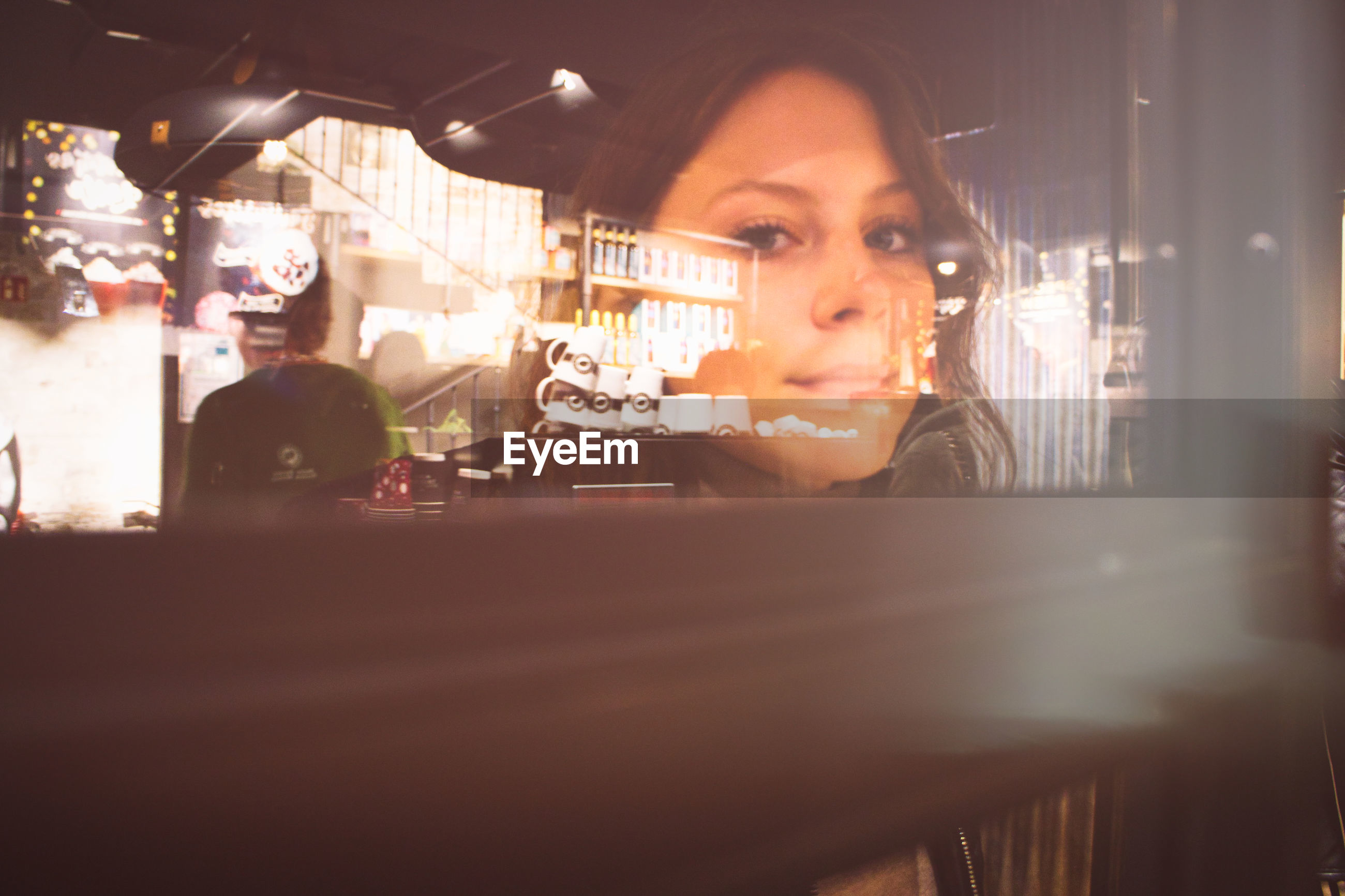 Close-up portrait of young woman in illuminated restaurant seen through window