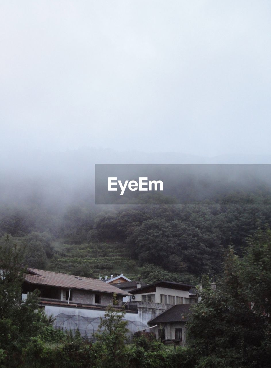 Houses on mountains during foggy weather