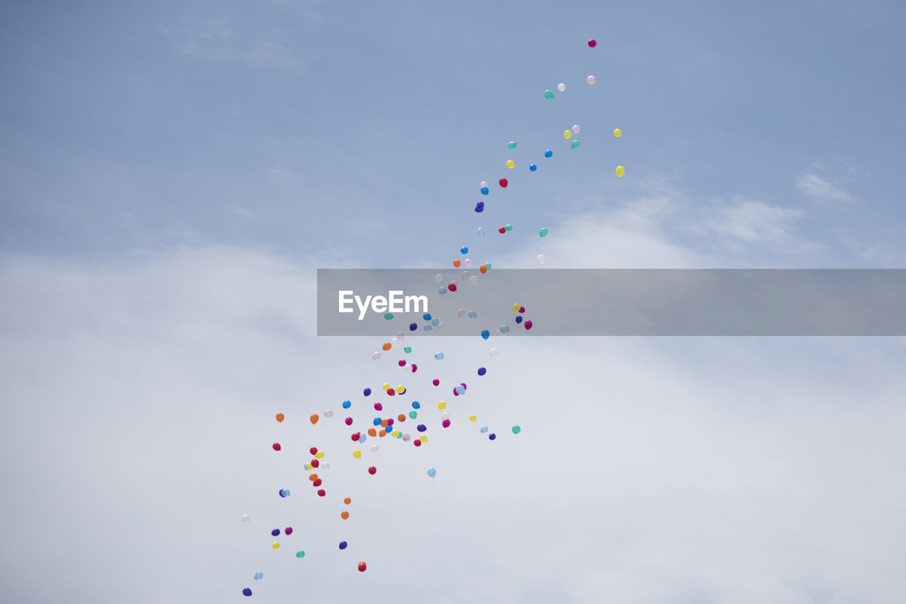 Low Angle View Of Multi Colored Balloons Flying In Sky
