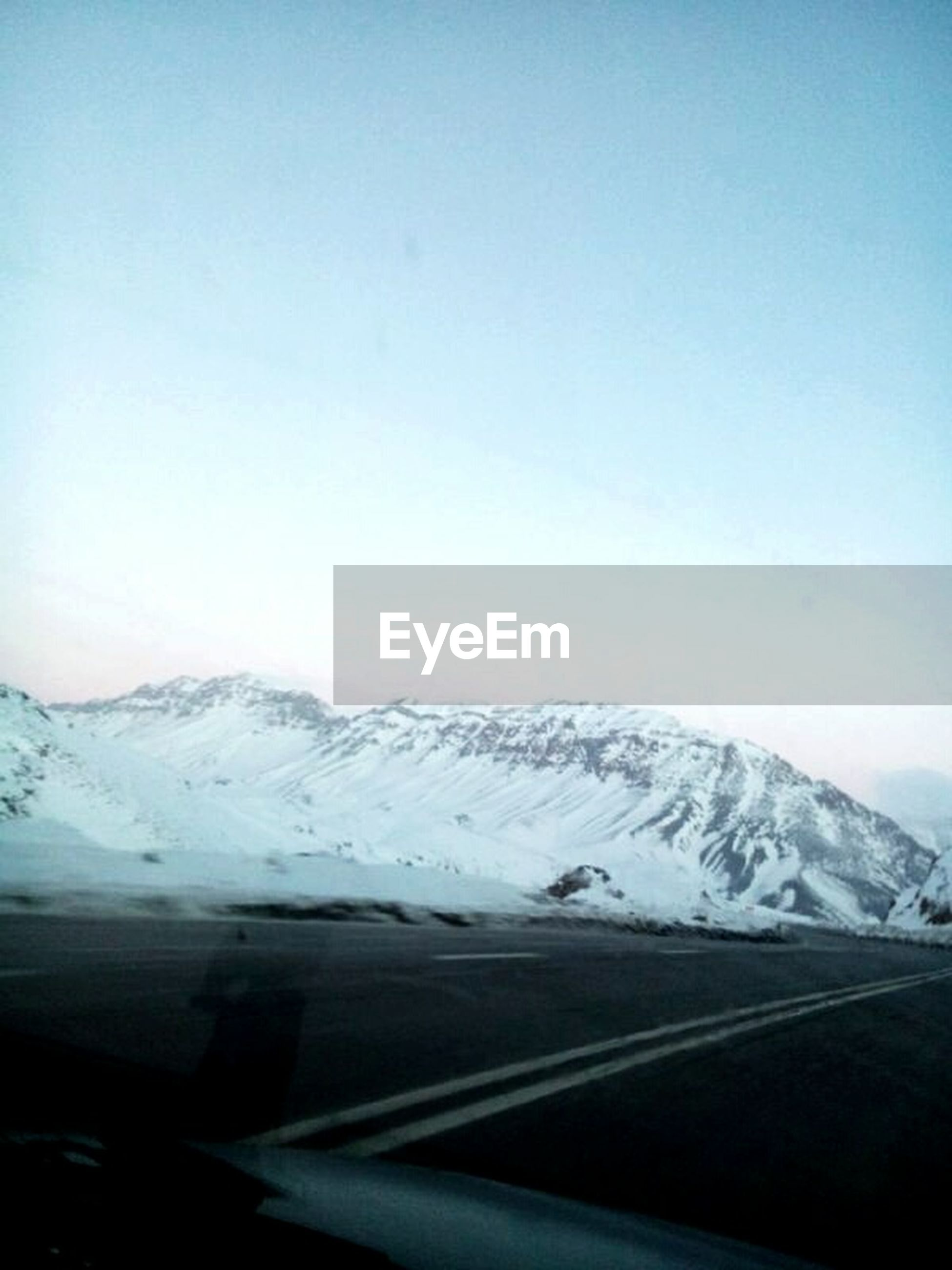 transportation, mountain, cold temperature, winter, snow, clear sky, car, season, land vehicle, road, mode of transport, copy space, mountain range, scenics, tranquil scene, snowcapped mountain, non-urban scene, majestic, journey, nature, beauty in nature, tranquility, vacations, physical geography, blue, day, remote
