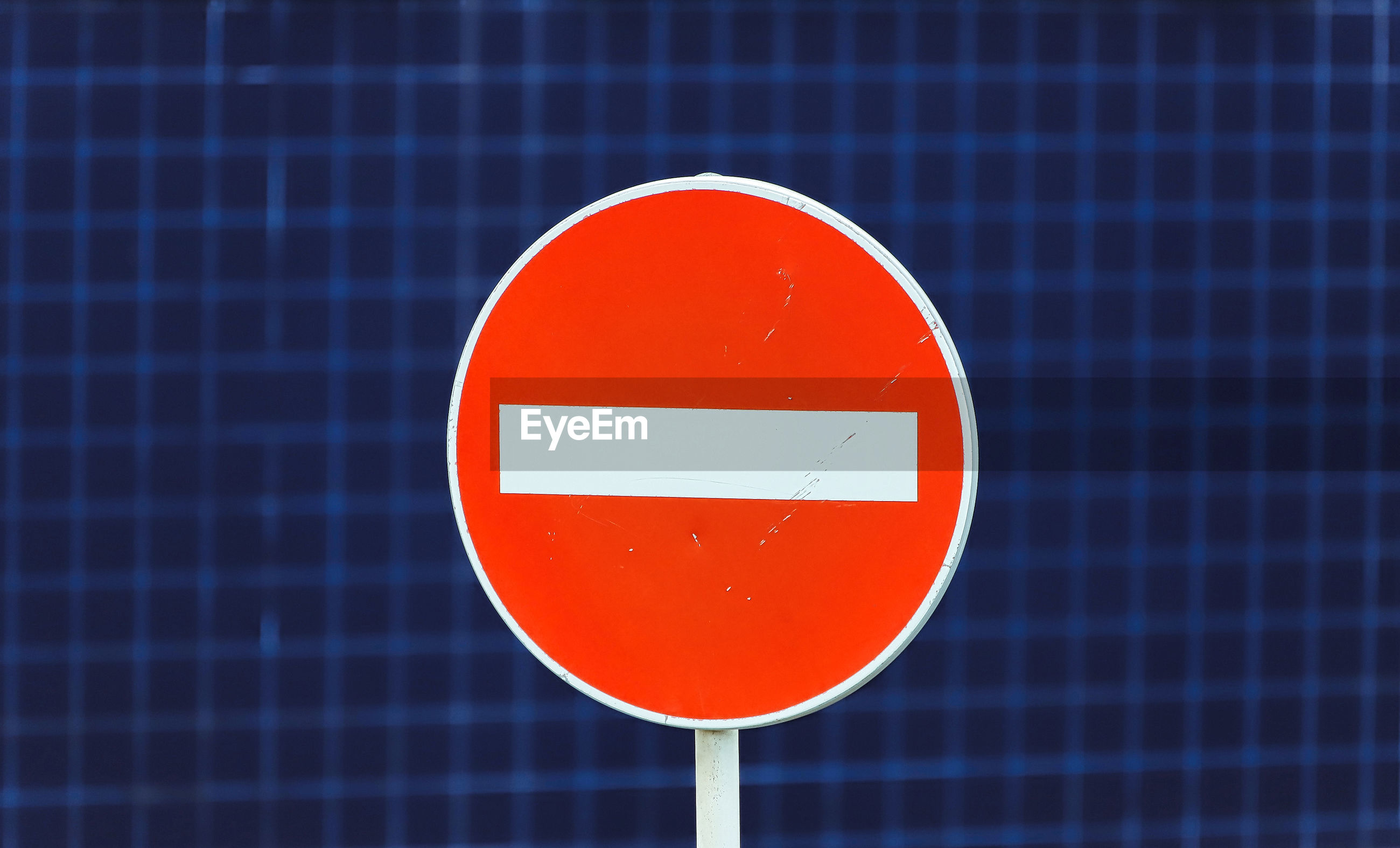 Close-up of do not enter sign against blue wall