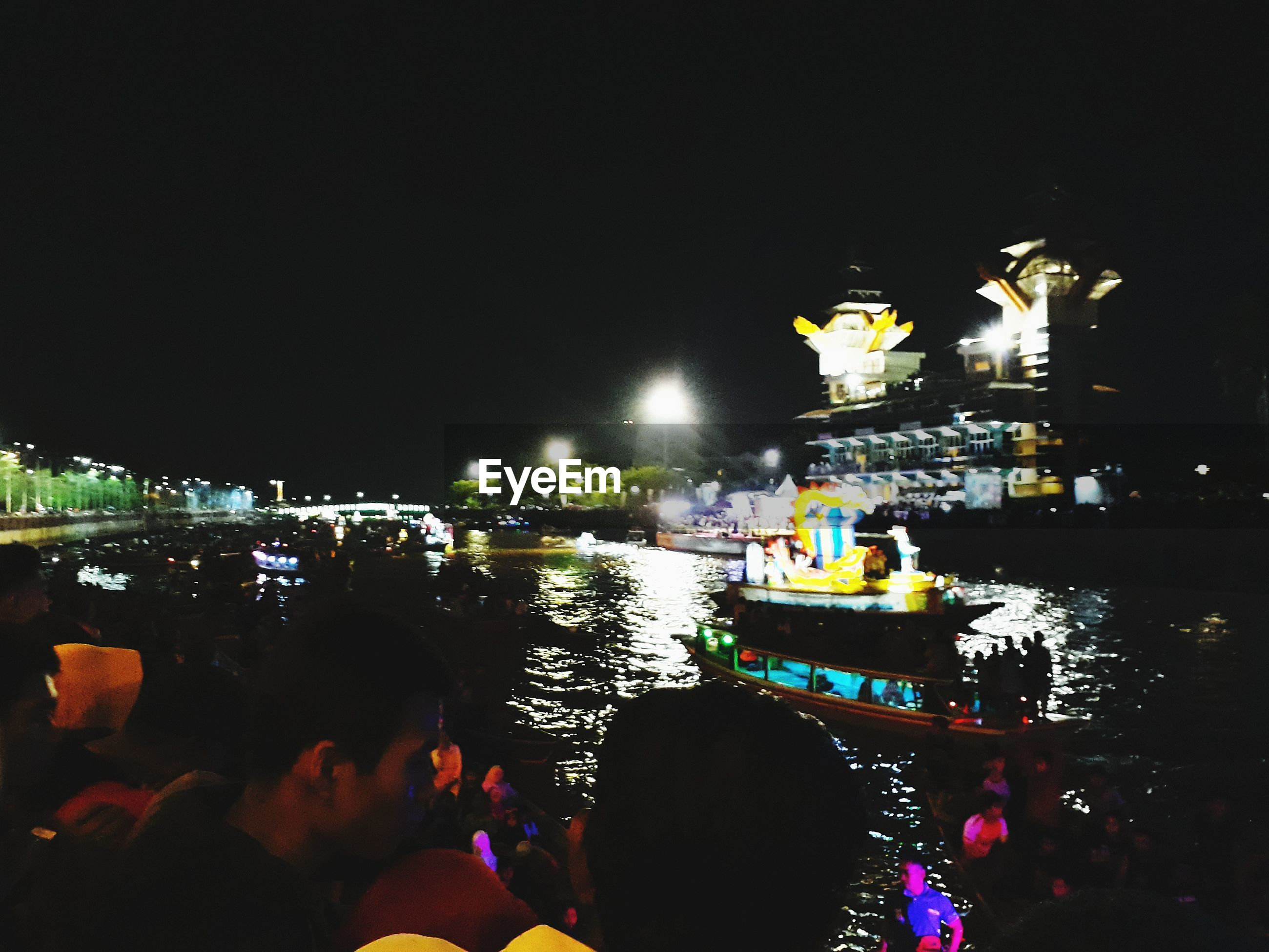 illuminated, night, built structure, architecture, building exterior, city, real people, city life, lifestyles, leisure activity, large group of people, water, nightlife, outdoors, cityscape, sea, men, crowd, nautical vessel, sky, people