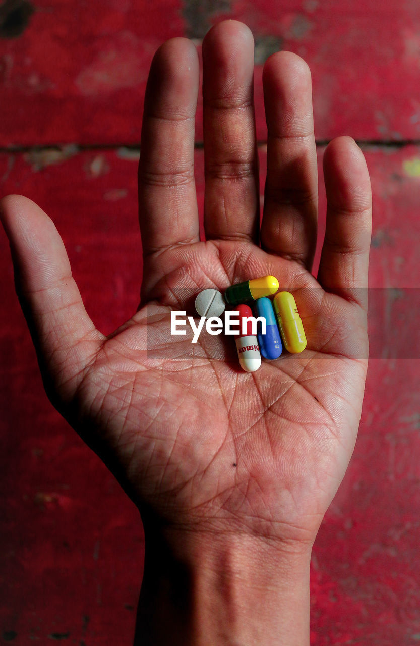 Cropped hand holding multi colored pills