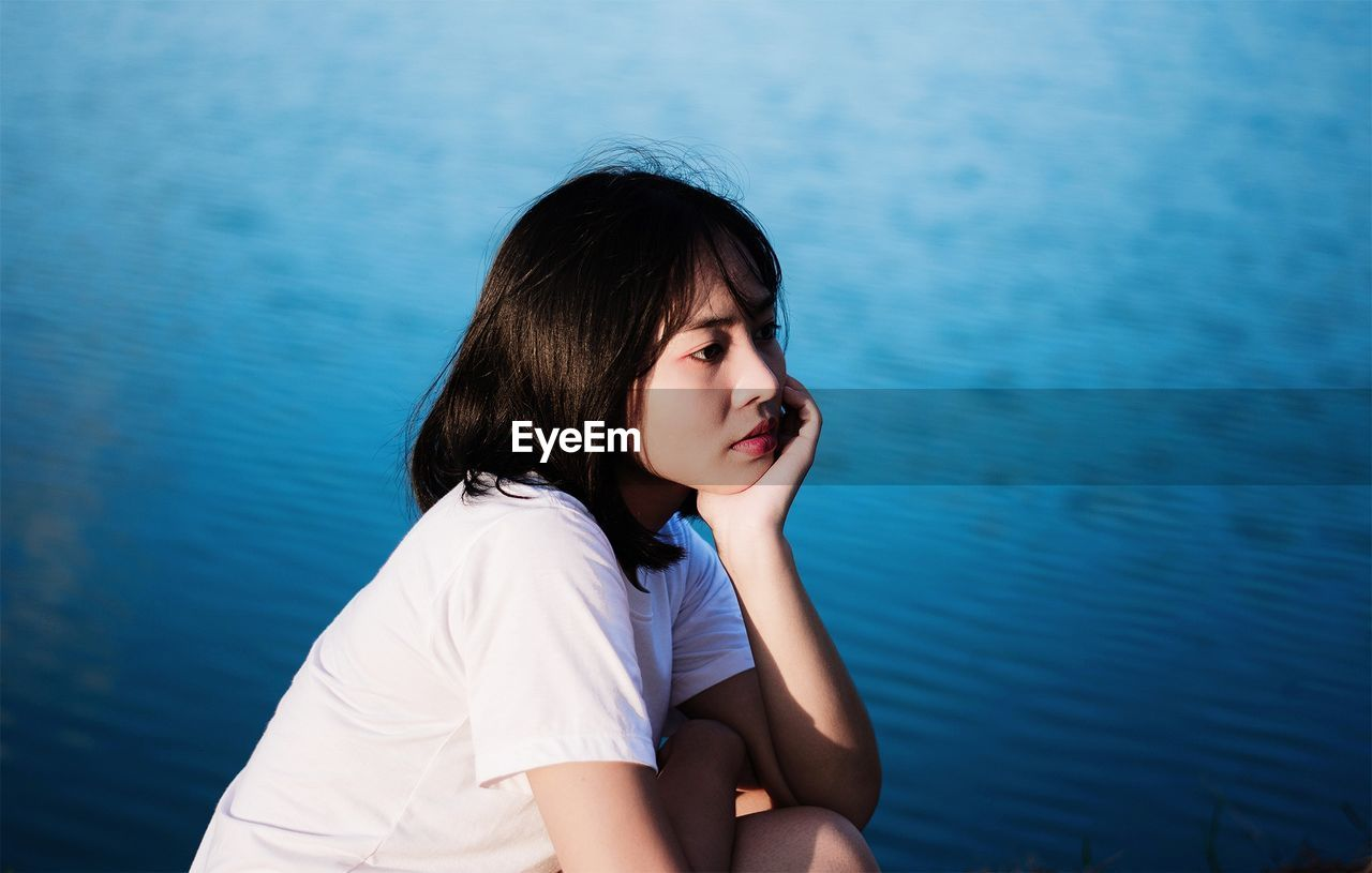 Thoughtful Woman Sitting By Sea
