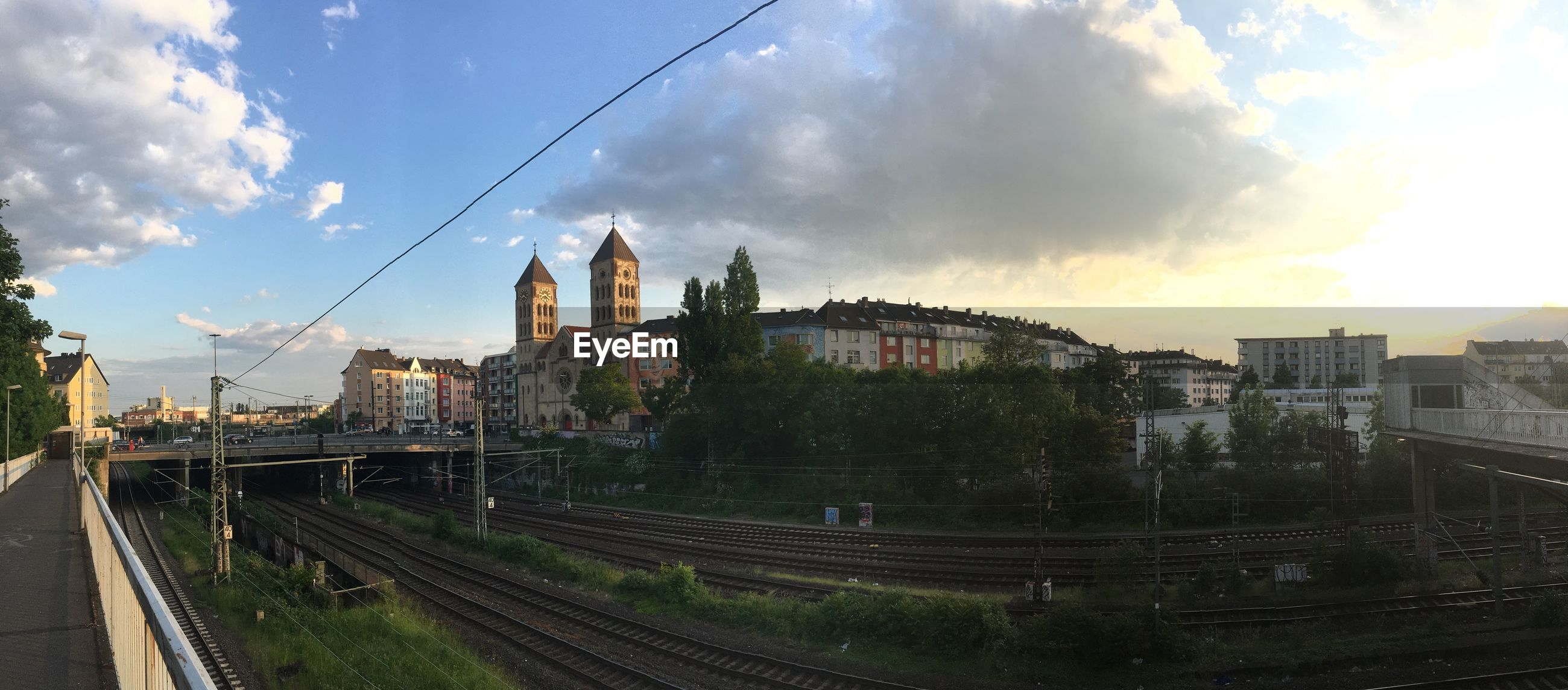 Panoramic view of railroad tracks by buildings in city against sky