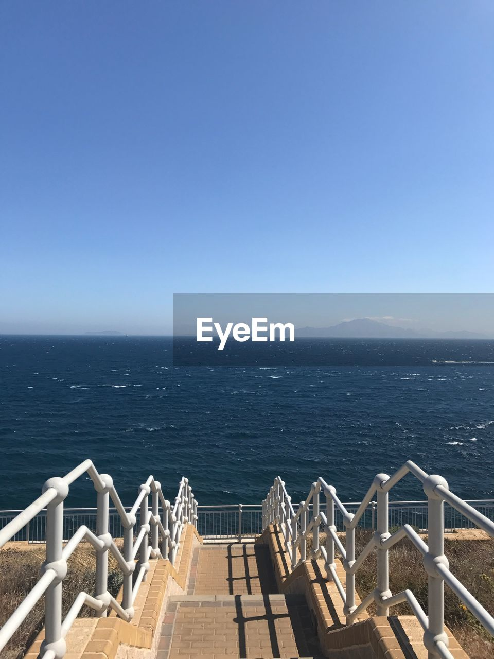 High Angle View Of Staircase By Sea Against Clear Sky
