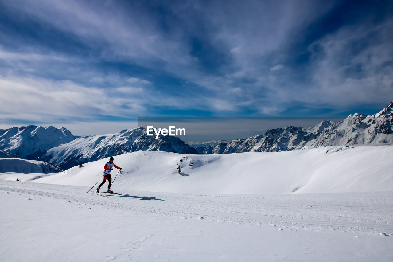Mature Man Skiing On Snow Covered Landscape Against Sky