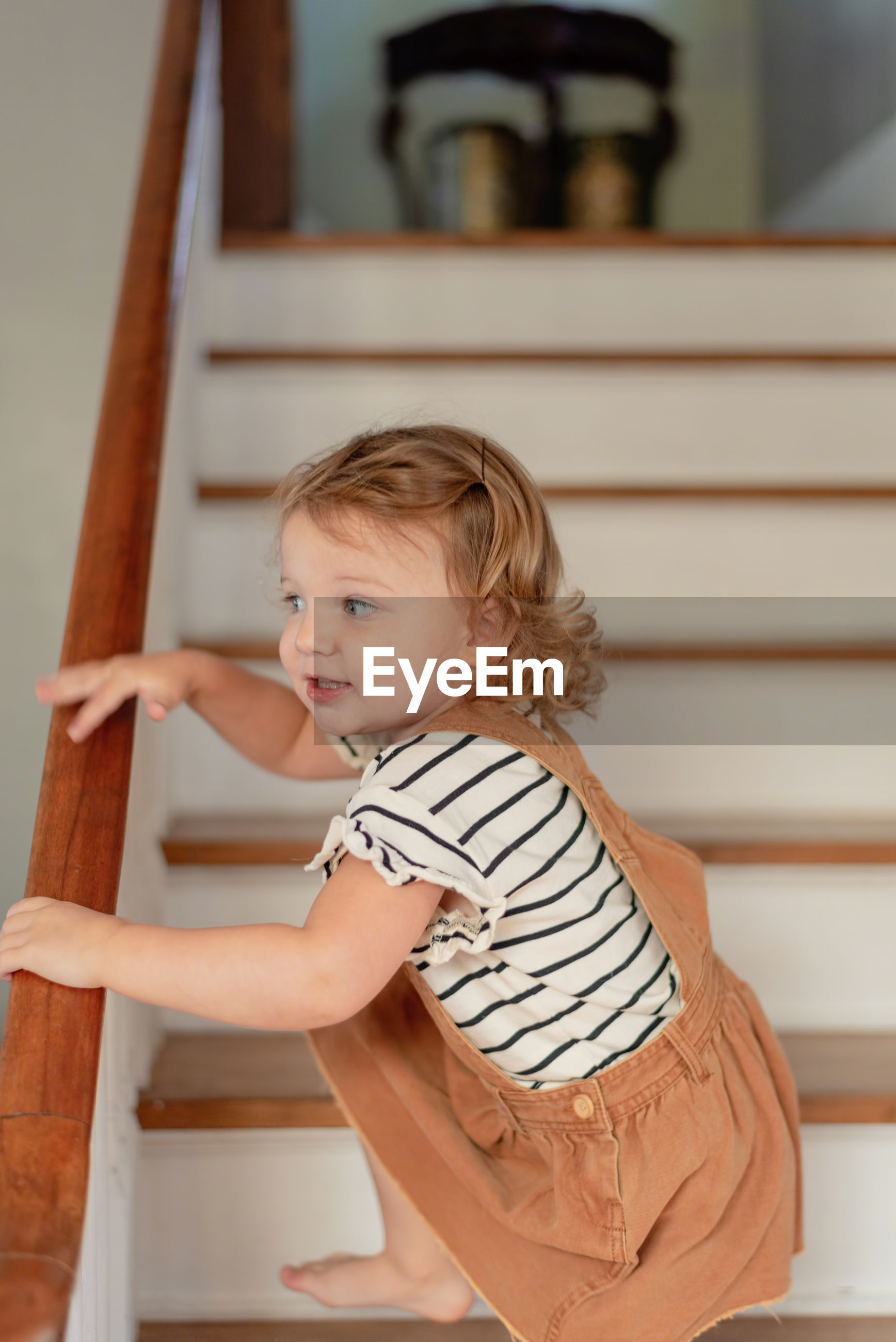 Side view of cute girl climbing on staircase at home