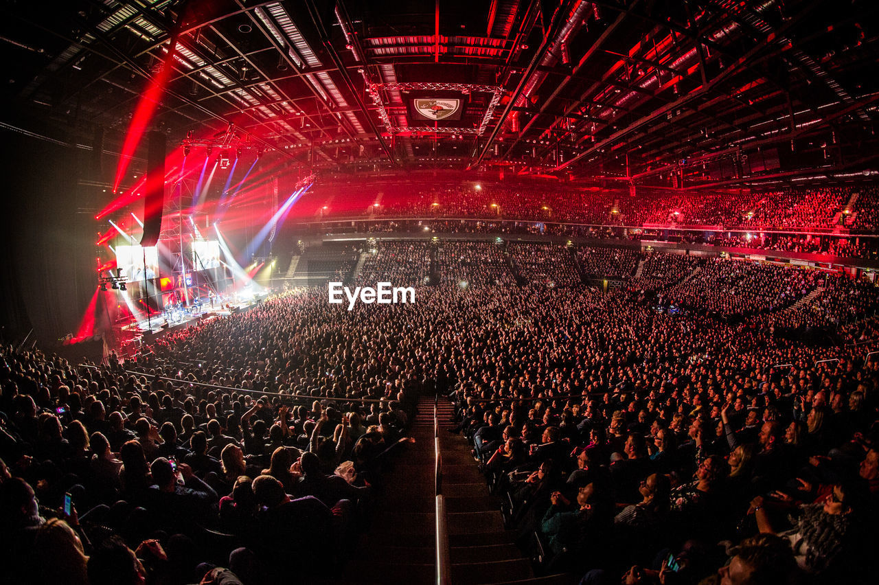 large group of people, crowd, illuminated, audience, stage light, arts culture and entertainment, stage - performance space, popular music concert, event, night, fun, excitement, stadium, music, togetherness, men, performance, fan - enthusiast, real people, indoors, people, adult, adults only