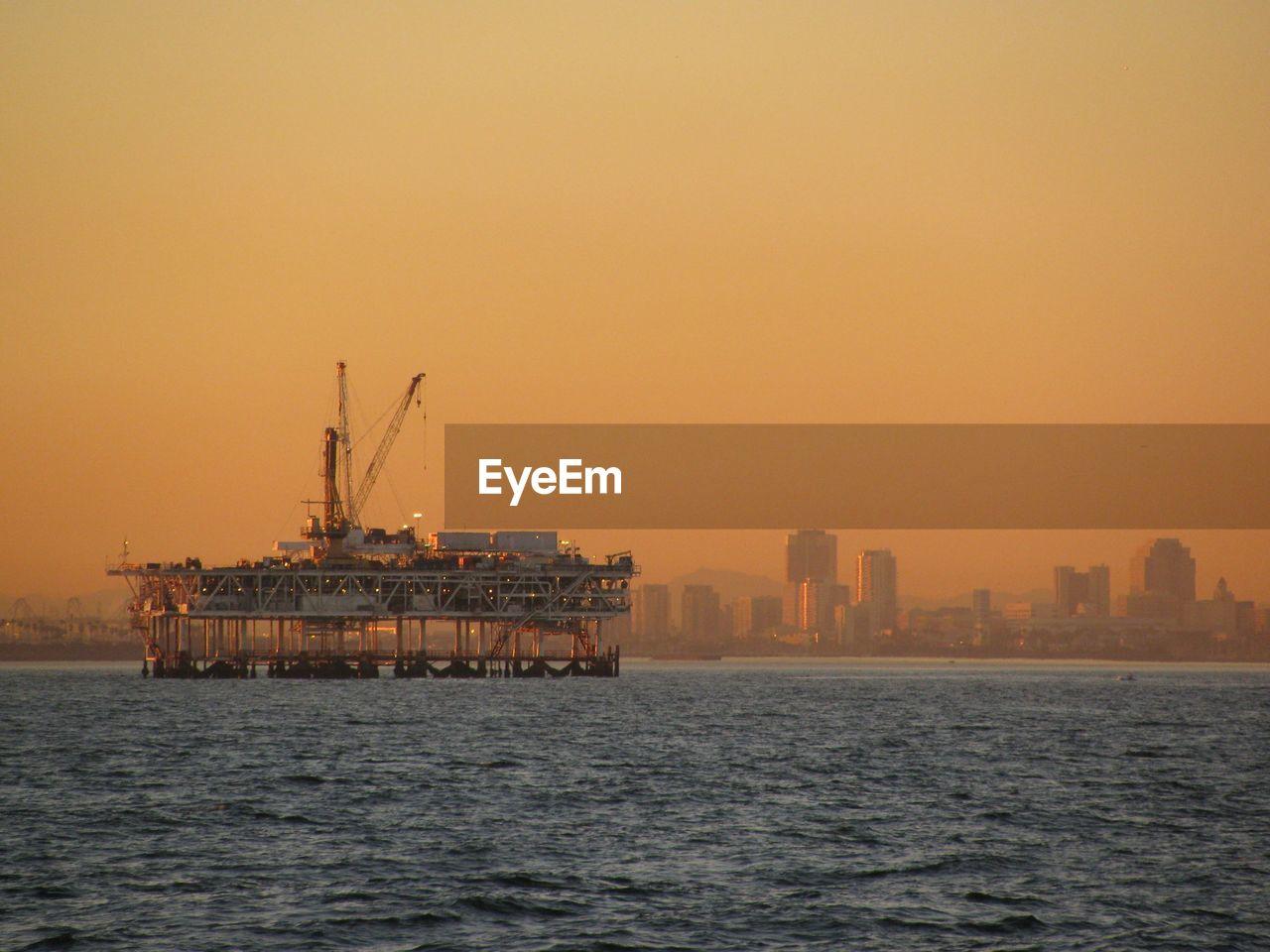 Offshore Platform Amidst Sea Against Orange Sky
