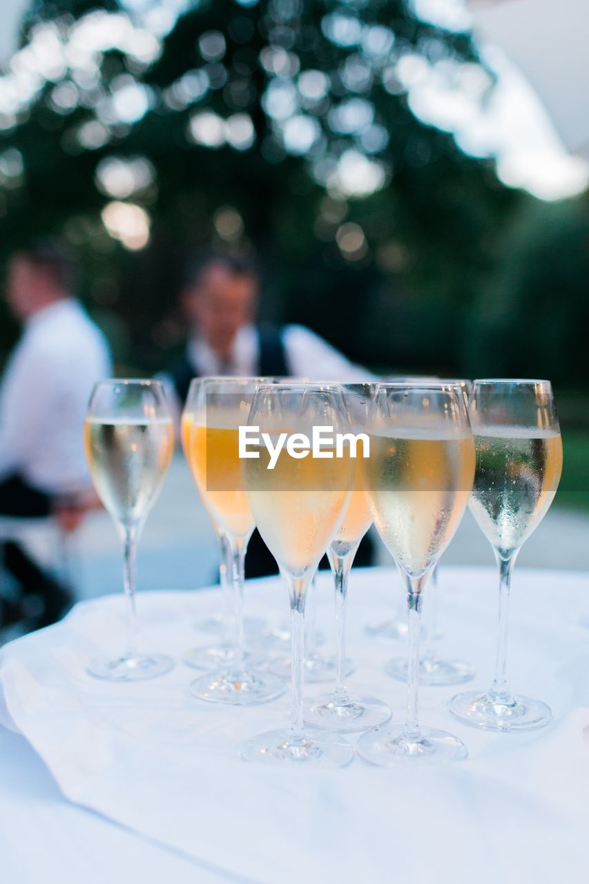 drink, refreshment, alcohol, food and drink, glass, focus on foreground, glass - material, table, wine, wineglass, champagne, real people, champagne flute, drinking glass, transparent, household equipment, freshness, incidental people, close-up, white wine, tray