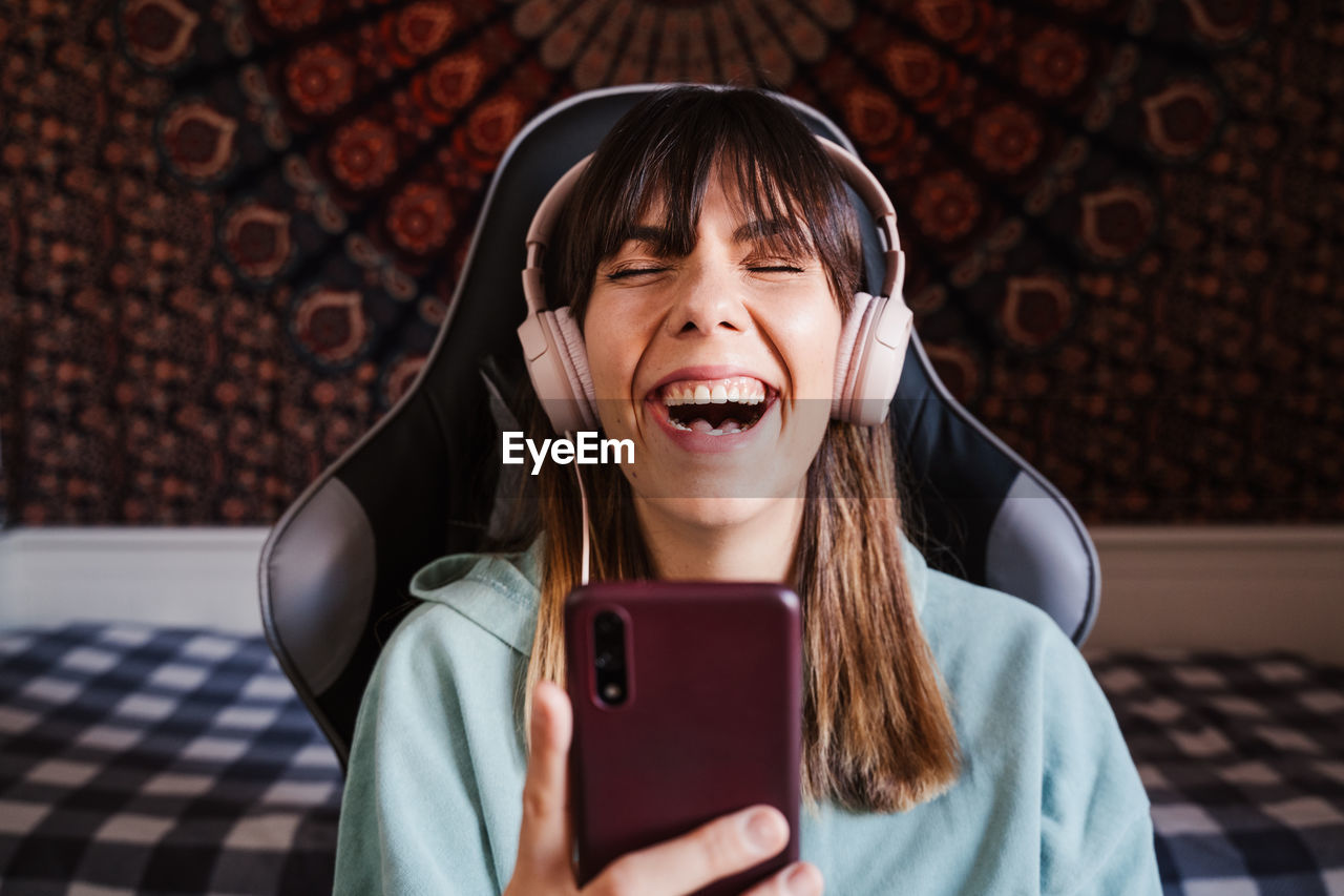 Smiling young woman video conferencing over mobile phone