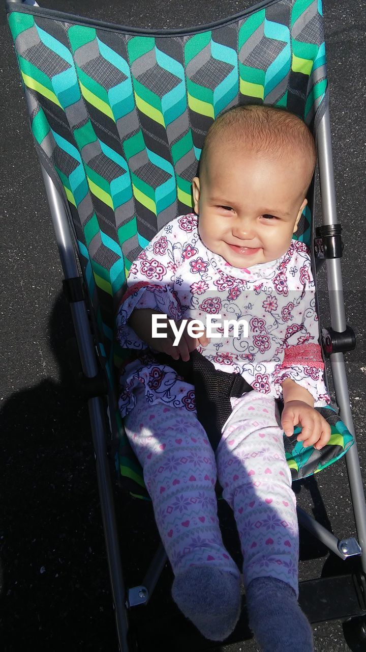 Portrait Of Cute Toddler In Baby Carriage On Road During Sunny Day