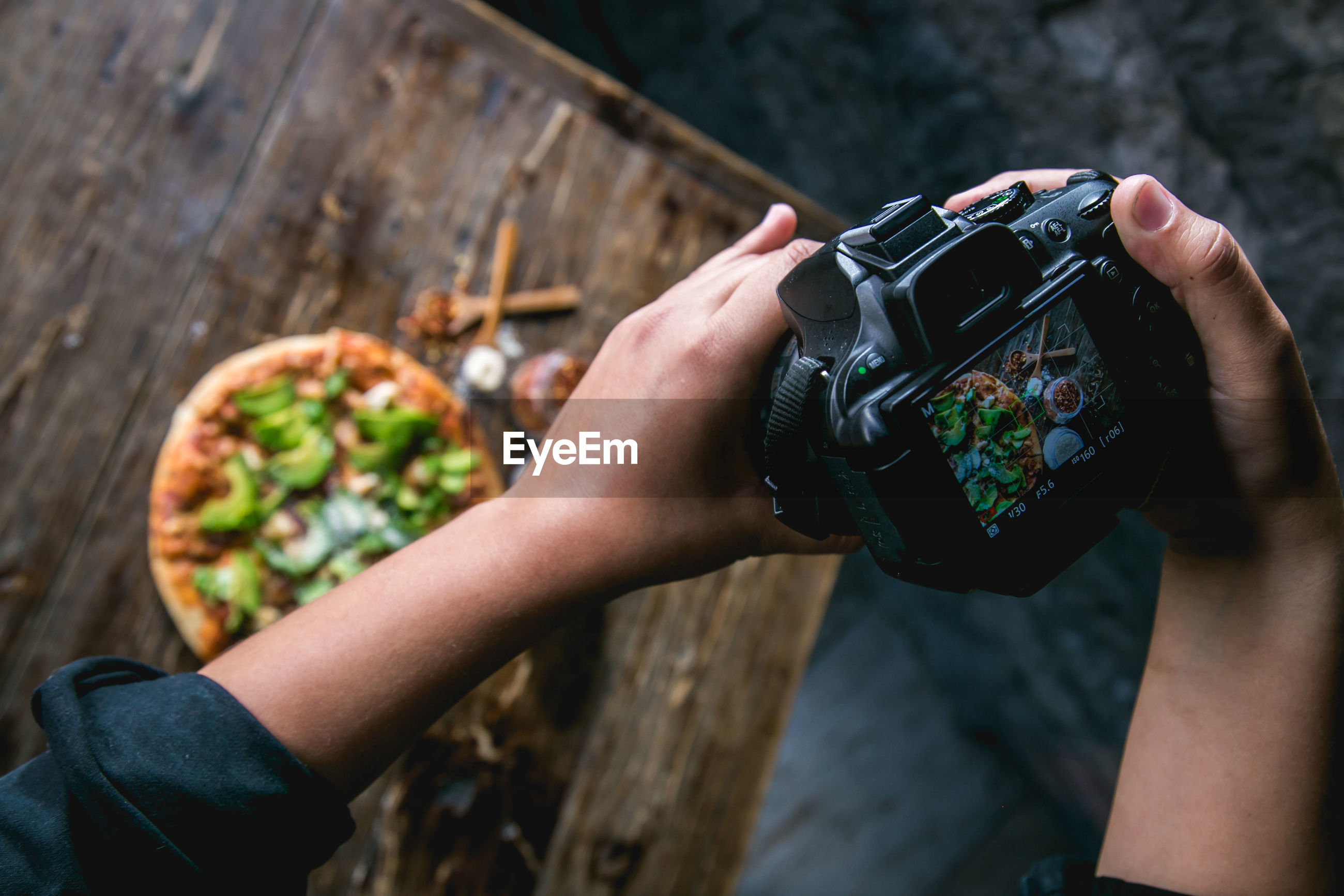 Cropped hands photographing pizza using camera