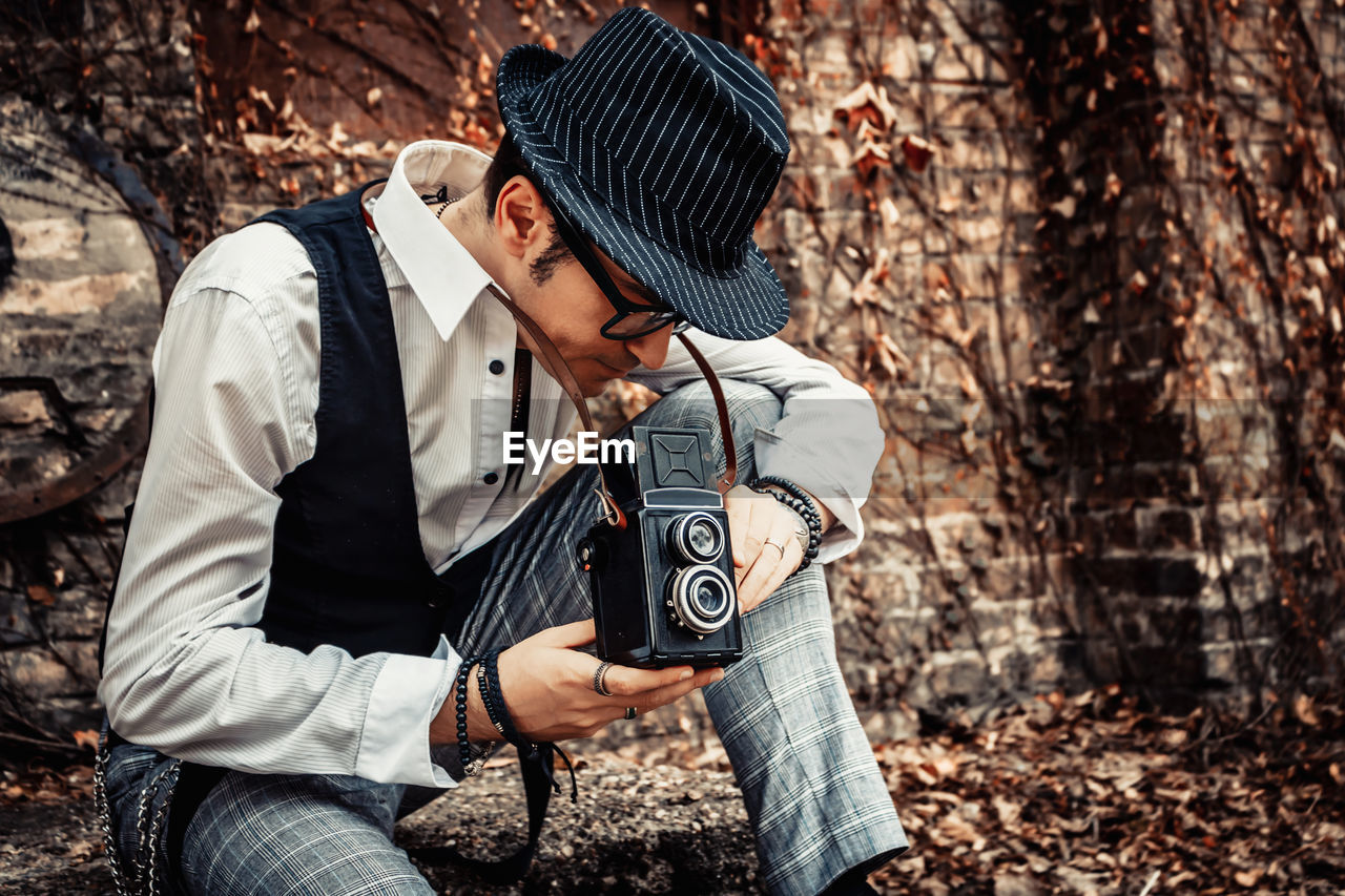 Retro-styled man taking picture with vintage medium format photo camera outdoors.
