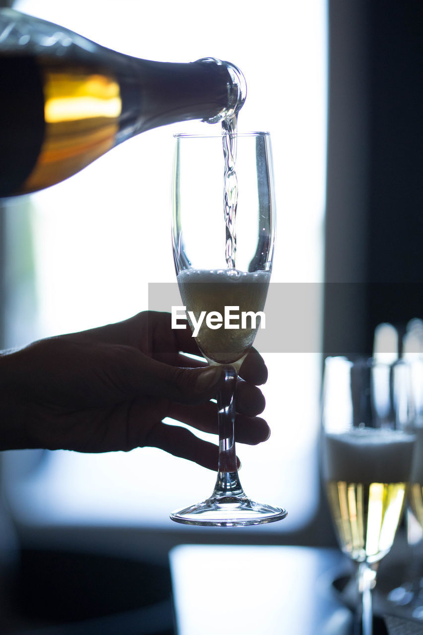 Cropped hands pouring champagne in flute from bottle