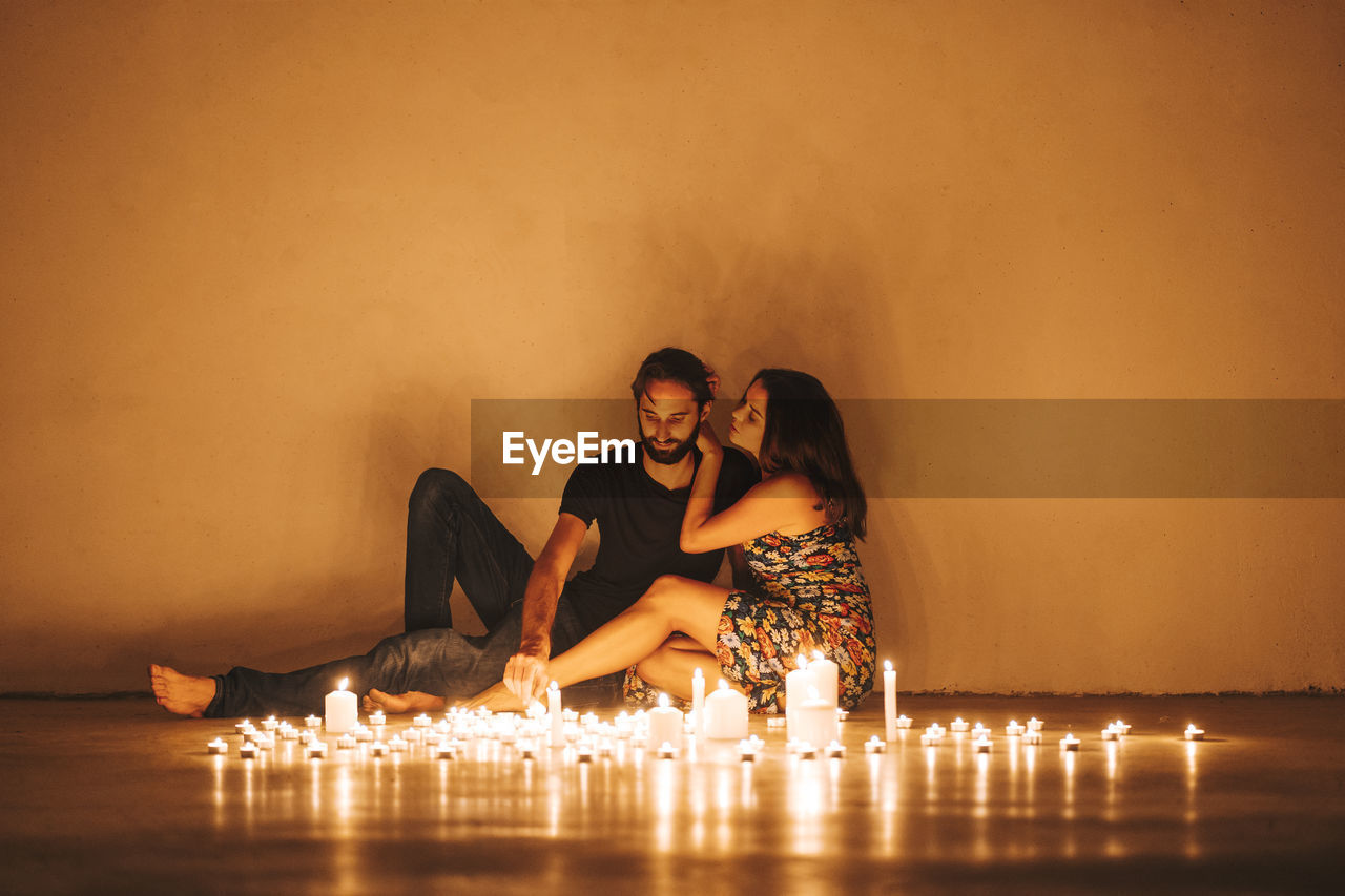 YOUNG COUPLE SITTING ON WALL AT ILLUMINATED ROOM