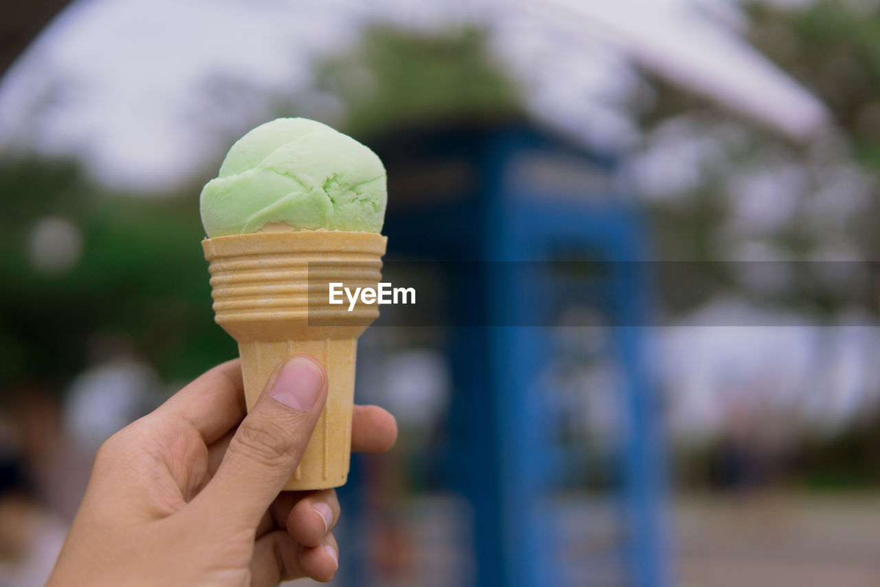 CROPPED HAND HOLDING ICE CREAM CONE AGAINST BLURRED BACKGROUND