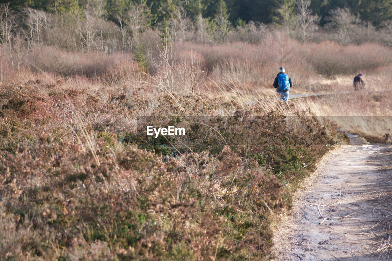 Rear View Of People Hiking On Field