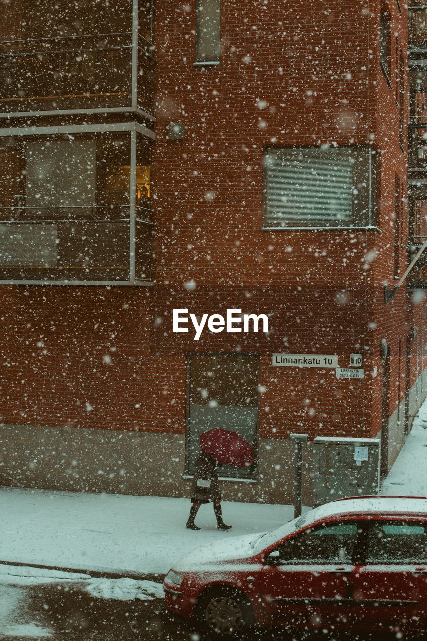 snow, winter, snowing, cold temperature, building exterior, architecture, city, built structure, storm, blizzard, walking, mode of transportation, street, day, motor vehicle, car, transportation, nature, motion, extreme weather, outdoors, warm clothing, rain