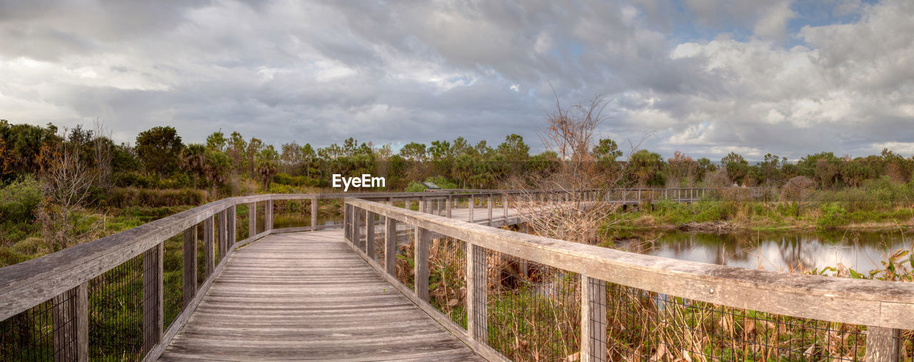 cloud - sky, tree, sky, direction, connection, plant, wood - material, the way forward, nature, tranquility, water, railing, tranquil scene, scenics - nature, boardwalk, bridge, no people, beauty in nature, non-urban scene, outdoors, diminishing perspective, wood, footbridge