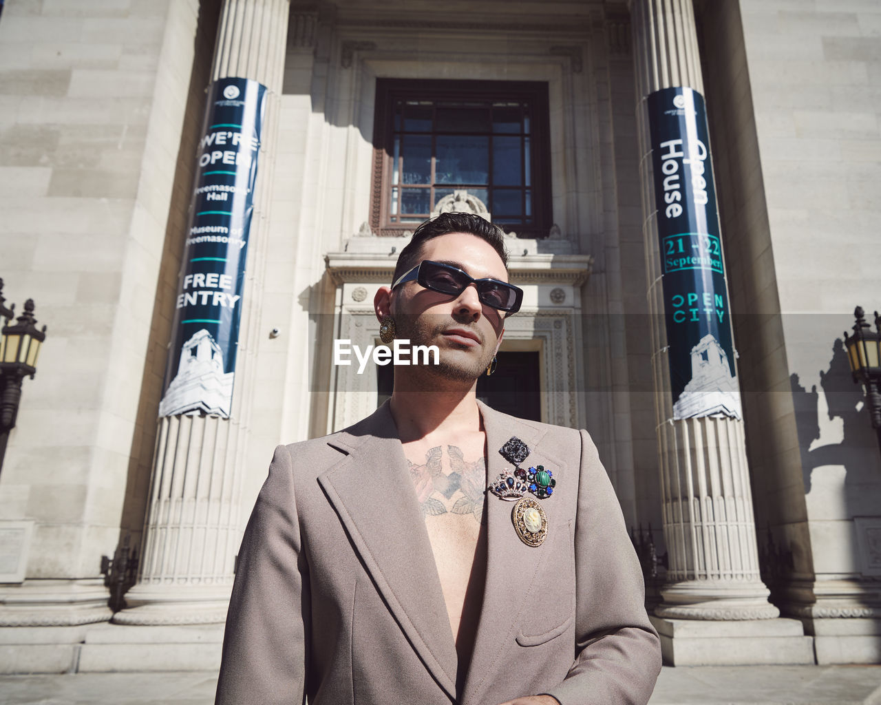 architecture, one person, built structure, building exterior, young adult, front view, young men, glasses, real people, sunglasses, waist up, portrait, city, lifestyles, day, leisure activity, standing, fashion, outdoors, architectural column