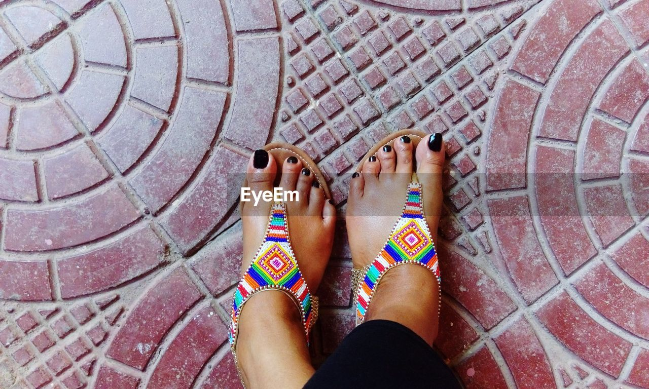 Low Section Of Woman Wearing Multi Colored Slippers