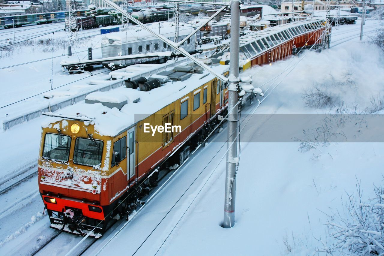 High Angle View Of Locomotive On Snowcapped Railroad Track During Winter